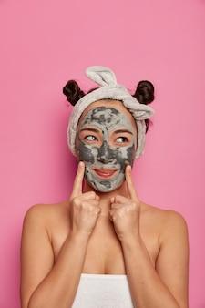 Молодая женщина носит маски для лица из натуральной глины для ухода за кожей после принятия ванны