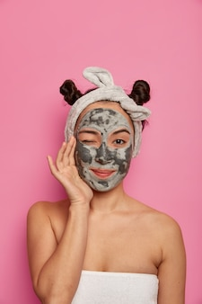 Young woman wears natural facial clay mask skin treatments after taking bath