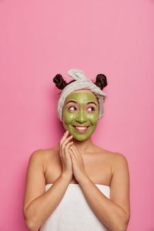 젊은 여자는 목욕 후 천연 페이셜 마스크 스킨 트리트먼트를 착용