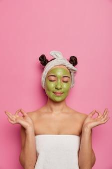 Молодая женщина носит натуральные маски для лица для ухода за кожей после принятия ванны