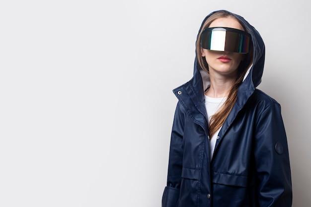 젊은 여성은 밝은 배경에 파란색 재킷을 입고 가상 현실 안경을 착용합니다.
