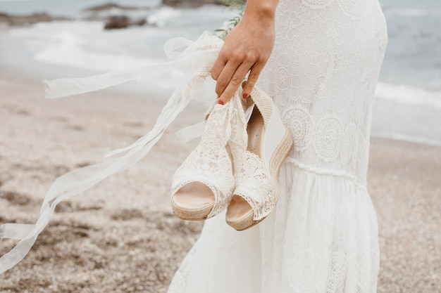 Young woman in wedding dress at the beach