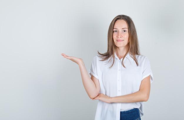 젊은 여자를 환영하거나 흰색 티셔츠, 청바지에 뭔가를 보여주는 쾌활한 찾고