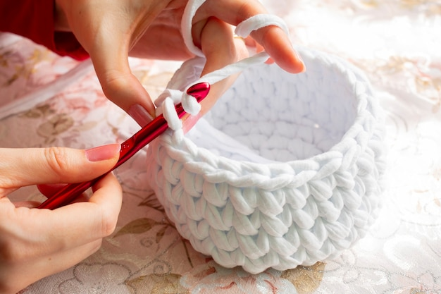 T- 셔츠 원사로 crocheting 동안 젊은 여자.