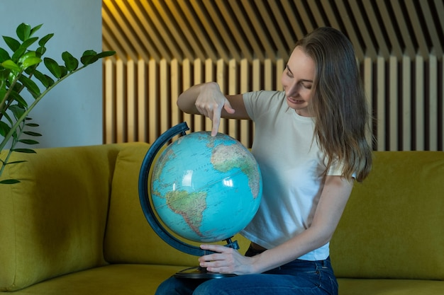 Young woman while sitting on sofa at home holding a world globe choose a route of travel