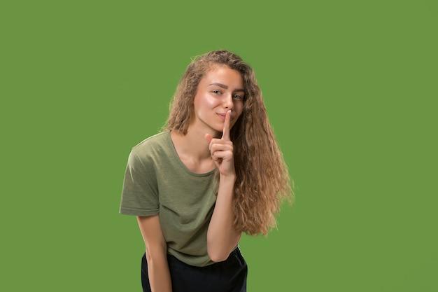 彼女の手の後ろに秘密をささやく若い女性。トレンディな緑のスタジオの背景に分離された女性。