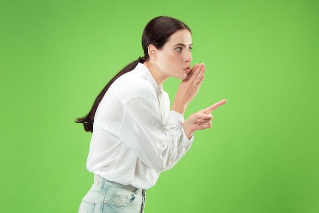 Молодая женщина шепчет секрет за ее рукой
