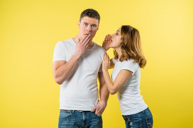Young woman whispering something in shocked boyfriend's ear
