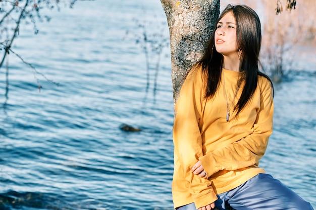 ヒップホップスタイルの若い女性は、湖の近くの自然の中でリラックスします。
