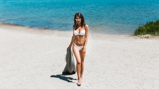 Young woman in white bikini carrying scarf