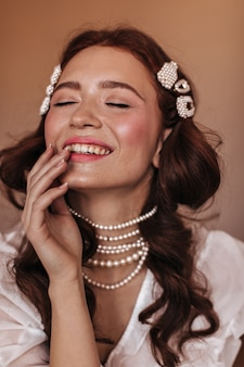 Young woman in white blouse and pearl jewelry laughs. snapshot of woman with freckles on beige background.
