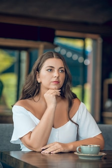 Young woman in white blouse with an impatient look sitting in summer cafe in afternoon