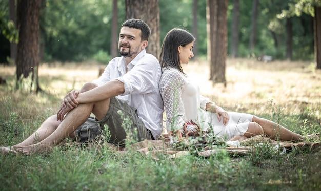 Una giovane donna in abito bianco e un uomo in camicia sono seduti nella foresta sull'erba, un appuntamento in natura, una storia d'amore nel matrimonio.