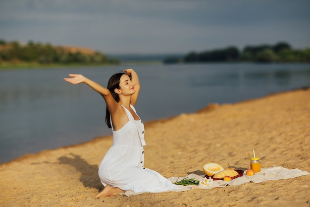 Young woman in white dress sitting on the sandy beach with hands up and enjoying summer picnic