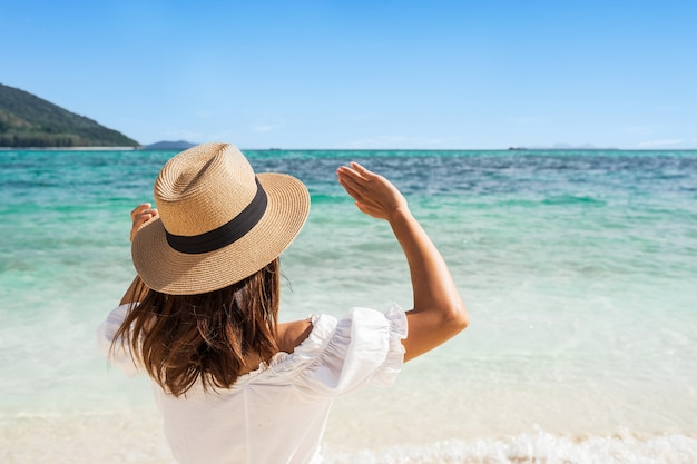 Young woman in white dress and straw hat raising her arms at the beach