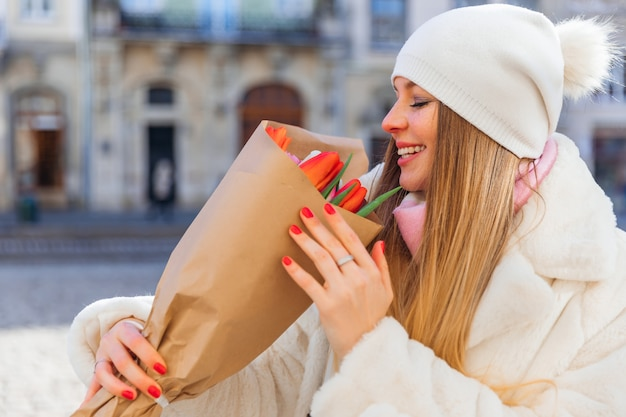 Young woman in white fur coat and hat holding a beautiful bouquet of tulips city street profile