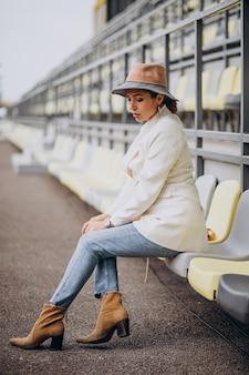 Giovane donna in giacca bianca tenendo il cappello