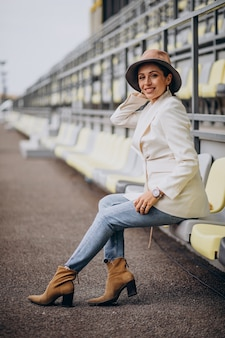 Young woman in white jacket holding hat