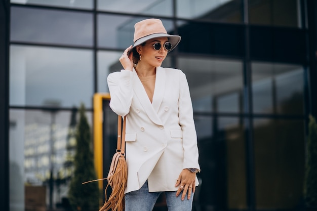 Young woman in white jacket walking outdoors