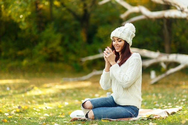 Young woman in white knitted sweather and hat, drink hot coffee in autumn forest at fallen tree .