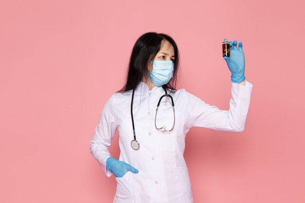 Giovane donna in tuta medica bianco guanti blu maschera protettiva blu in possesso di pillole colorate su rosa