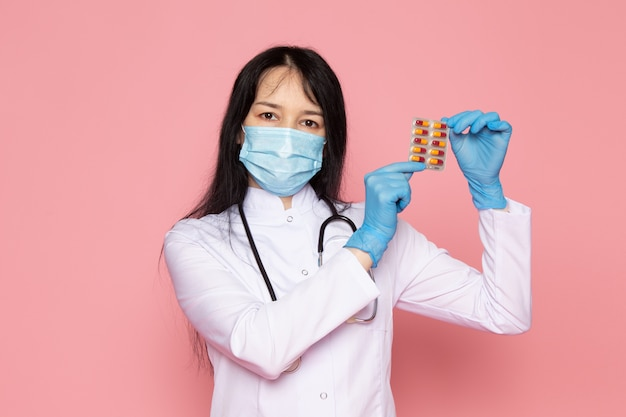 Young woman in white medical suit blue gloves blue protective mask holding multicolroed pills on pink