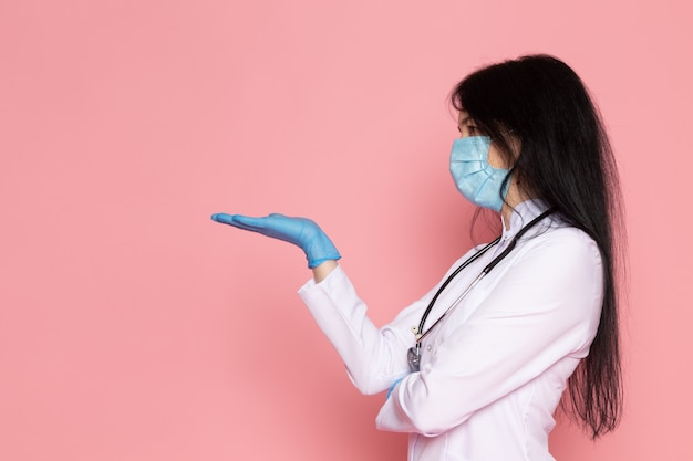 Young woman in white medical suit blue gloves blue protective mask long hair stethoscope on pink