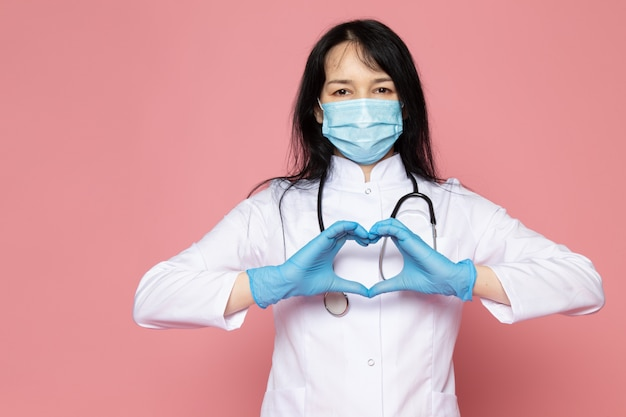 Young woman in white medical suit blue gloves blue protective mask with stethoscope on pink