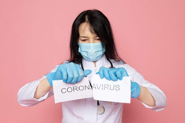 Young woman in white medical suit blue gloves blue protective mask with stethoscope tearing coronavirus word on pink