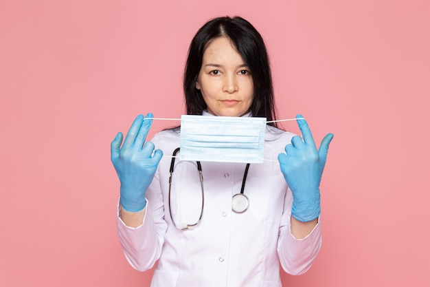 Young woman in white medical suit blue gloves with stethoscope on pink