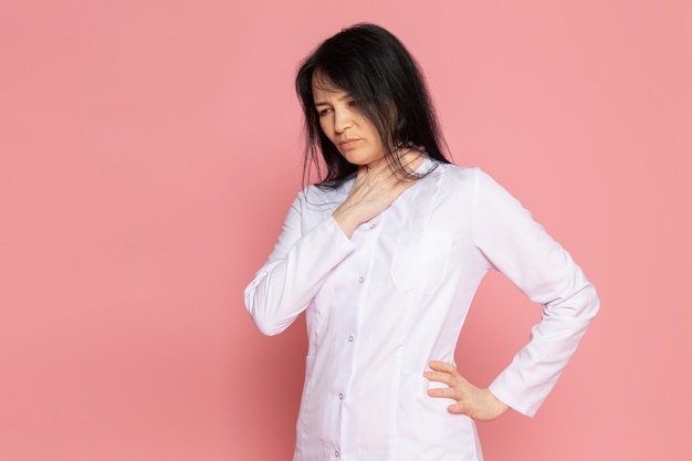 Young woman in white medical suit having breath troubles on pink