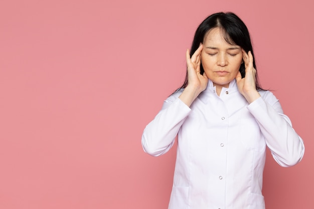 Young woman in white medical suit having a severe headache on pink