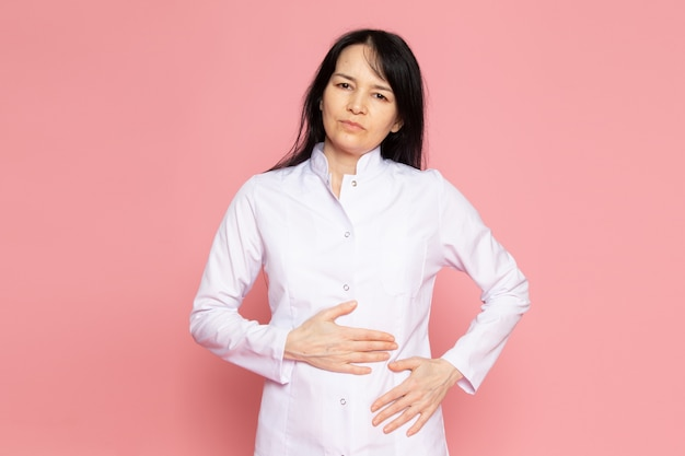 Young woman in white medical suit having a stomachache on pink