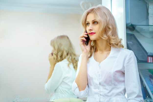 A young woman in a white robe calling on the phone in the office of a beautician.