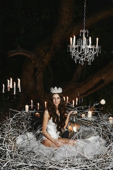 A young woman in white satin lingerie and a crown sits in a huge nest with candle lantern in her hand