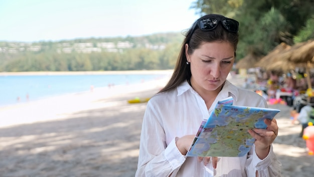 Young woman in a white shirt on the beach considers a map.