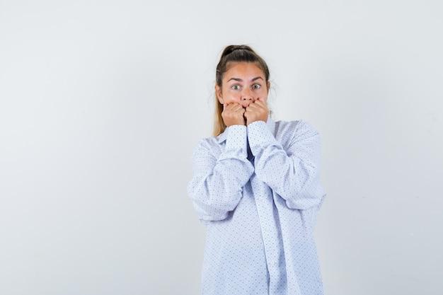 Giovane donna in camicia bianca che morde i pugni e che sembra sorpresa