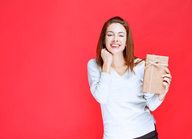 Giovane donna in camicia bianca che tiene in mano una scatola regalo di cartone e sembra sorpresa