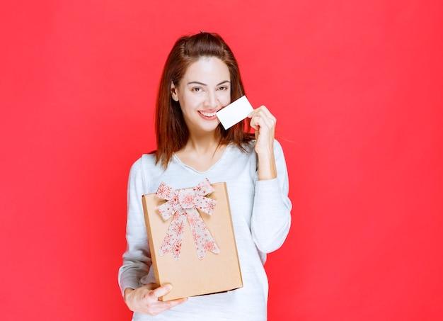 Giovane donna in camicia bianca che tiene una scatola regalo di cartone e presenta il suo biglietto da visita