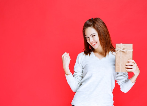 Young woman in white shirt holding a cardboard gift box and showing positive hand sign