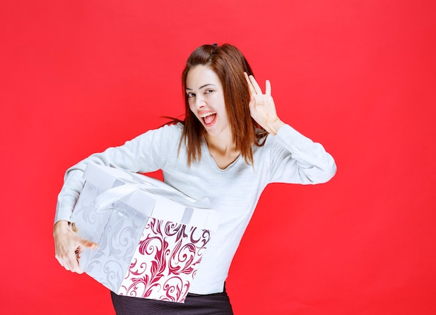 Giovane donna in camicia bianca che tiene in mano una scatola regalo stampata, urla e fa uscire la lingua