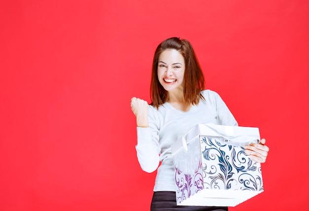 Giovane donna in camicia bianca che tiene in mano una confezione regalo stampata e mostra un segno positivo con la mano