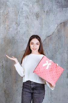 Giovane donna in camicia bianca con in mano una borsa della spesa rossa