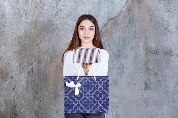 Giovane donna in camicia bianca con in mano una scatola regalo d'argento e una borsa della spesa blu