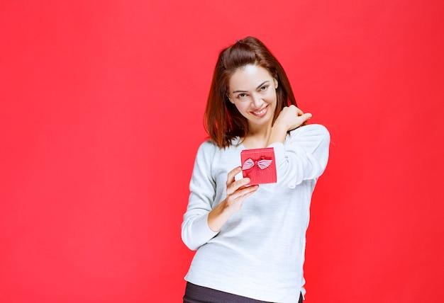 Giovane donna in camicia bianca con in mano una piccola scatola regalo rossa