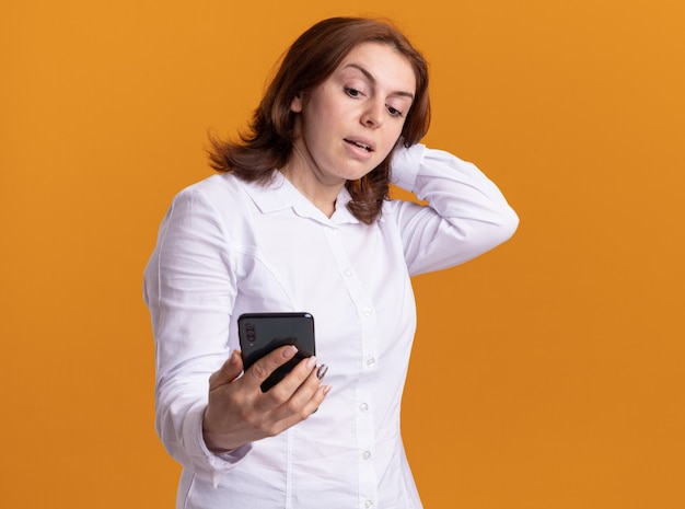 Young woman in white shirt holding smartphone looking at it being confused standing over orange wall