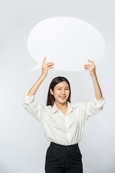 A young woman in a white shirt holding a thought box symbol