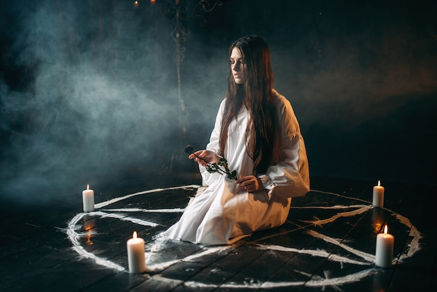 Young woman in white shirt holds burnt rose in hands, pentagram circle with candles, smoke all around. dark magic ritual, occultism