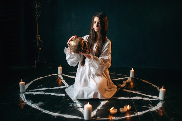 Young woman in white shirt holds human skull in hand, pentagram circle with candles, smoke all around, witch. dark magic ritual, occult