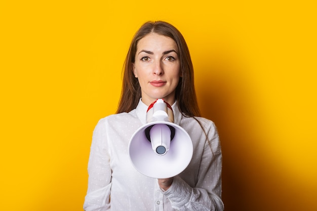 Young woman in a white shirt holds a megaphone in her hands on a yellow background